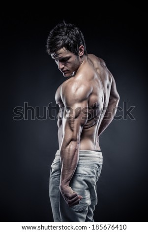 Strong Athletic Man Fitness Model posing back muscles, triceps, latissimus - stock photo