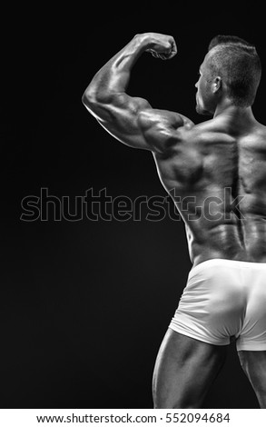 Strong Athletic Man Fitness Model posing back muscles, triceps, latissimus over black background