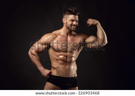 Strong Athletic Man Fitness Model Torso showing big muscles over black background - stock photo