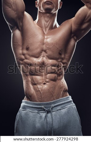 Strong athletic man fitness model torso showing six pack abs. Isolated on black background. - stock photo