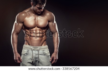 Strong Athletic Man Fitness Model Torso showing six pack abs. isolated on black background with copyspace - stock photo