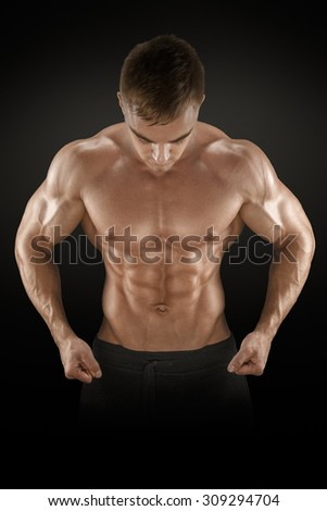 Strong athletic man fitness model torso showing six pack abs, perfect abs, shoulders, biceps, triceps and chest. Isolated on black background.  - stock photo