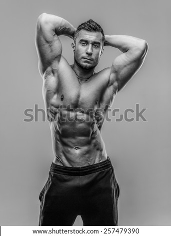 Strong athletic man flexing torso over gray background - stock photo