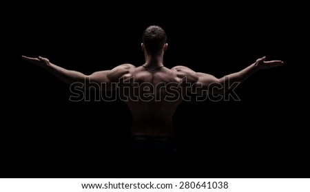 strong athletic man from back isolated over black background - stock photo