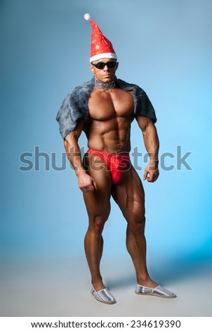 Strong athletic man in a santa hat and dark glasses. Bodybuilder on a blue background. Christmas fancy dress - stock photo