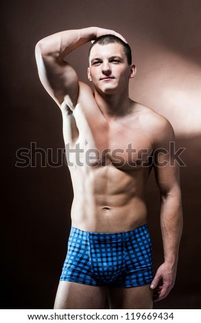 strong athletic man on broun background - stock photo