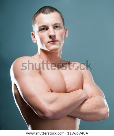 strong athletic man on grey background - stock photo
