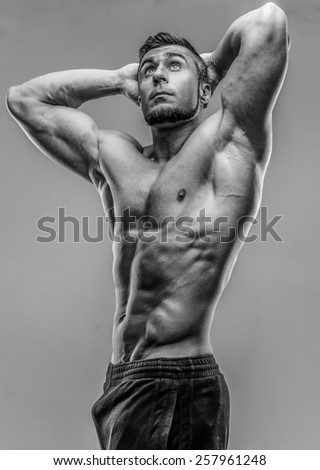 Strong athletic man posing over gray background. HDR monochrome - stock photo