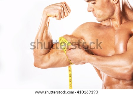 Strong Athletic Man showing muscular body and sixpack abs over white background.Muscular man on white background.Muscular man measuring his muscles - stock photo
