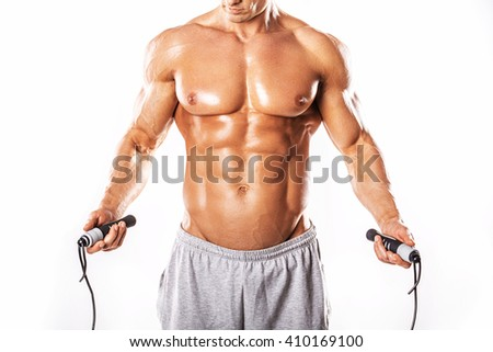 Strong Athletic Man showing muscular body and sixpack abs over white background. Portrait of muscular young man exercising with jumping rope.Muscular man on white background - stock photo