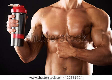 Strong Athletic Man showing muscular body on a black background.Muscular man on black background.muscular man with a shaker in hands on a black background - stock photo