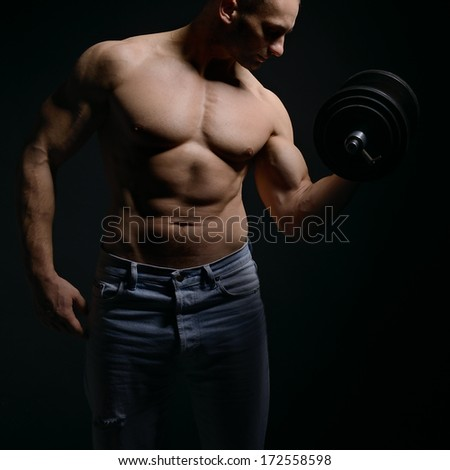strong athletic man with perfect body posing with dumbbells on black background  - stock photo