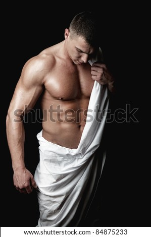strong athletic man with white cloth demonstrates his body on black background