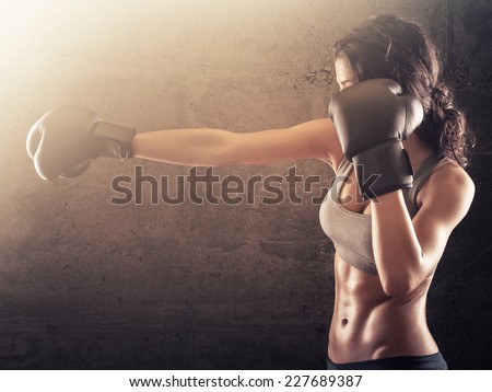 Strong athletic woman with boxing gloves punching