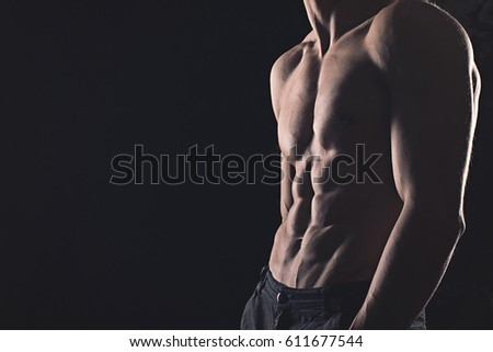 Strong athletic young man on black background