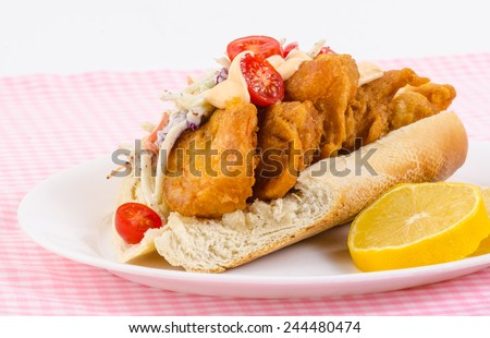 Strong back light on Beer-battered shrimp deep fried on bun with coleslaw and spicy mayonnaise spread with tomato and other Cajun Seasoning. - stock photo