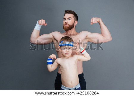Strong bearded man and his son standing and showing biceps over grey background - stock photo