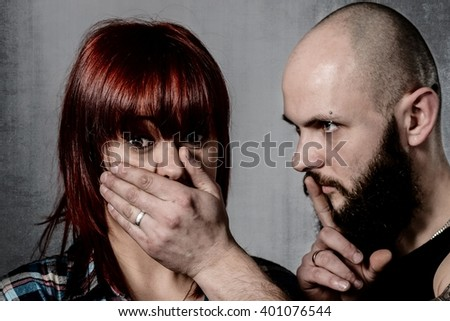 Strong bearded man covering woman face with emotional stress, pain, afraid, call for help, terrified expression. Domestic violence or kidnap, victim, hostage. - stock photo