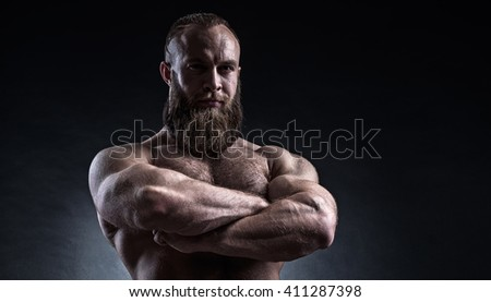 Strong bearded man with perfect abs, shoulders, biceps, triceps and chest. Bodybuilder topless over black background. - stock photo