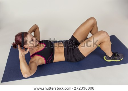 Strong Beautiful fitness woman doing crunches sit ups