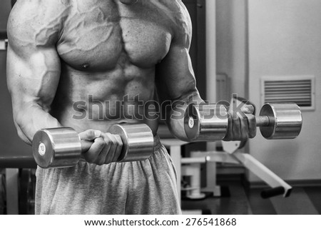 Strong beautiful man, pumping biceps. Training biceps dumbbells. Bodybuilder trains the muscles of the arms. - stock photo
