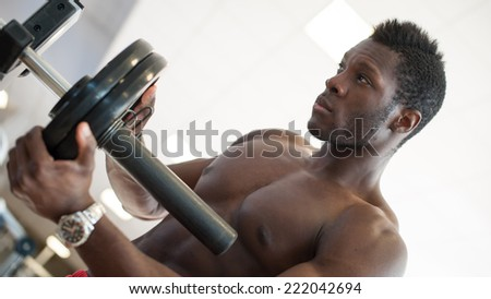 Strong black man adjusting heavy lift on bar in the gym.