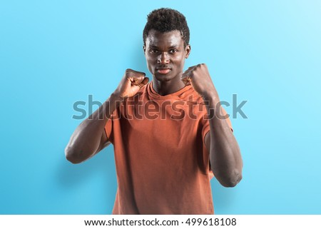 Strong black man giving a punch on blue background