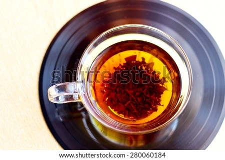 Strong black tea in glass cup on vinyl record disc - stock photo