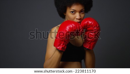 Strong Black Woman Athlete with boxing gloves on dark background - stock photo
