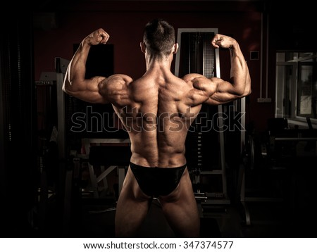 Strong bodybuilder flexing his back in the gym
