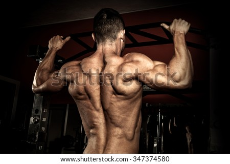 Strong bodybuilder in the gym doing pull ups - stock photo