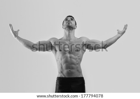 Strong bodybuilder man with perfect abs, shoulders,biceps, triceps and chest feeling great after a hard workout - stock photo