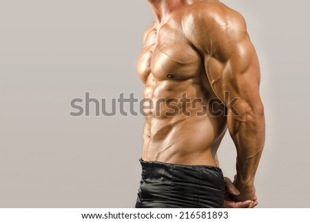 Strong bodybuilder man with perfect abs, shoulders,biceps, triceps and chest, personal fitness trainer
