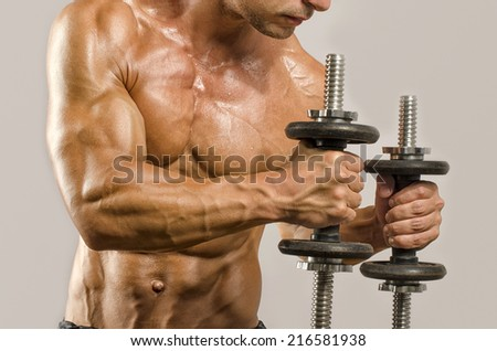 Strong bodybuilder man with perfect abs, shoulders,biceps, triceps and chest, personal fitness trainer training with heavy dumbbells - stock photo