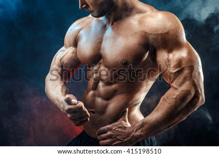 Strong bodybuilder man with perfect abs, shoulders,biceps, triceps, chest.