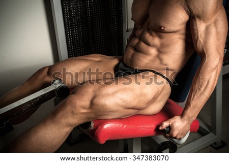 Strong bodybuilder training quads in the gym - stock photo