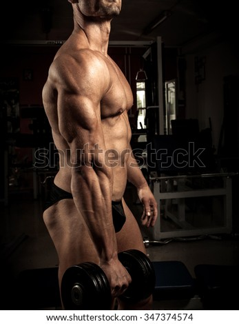 Strong bodybuilder with dumbbell in the gym - stock photo