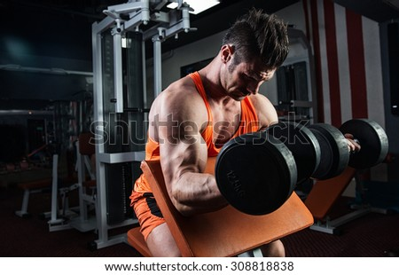 Strong bodybuilder with six pack, perfect abs, shoulders, biceps, triceps and chest - stock photo