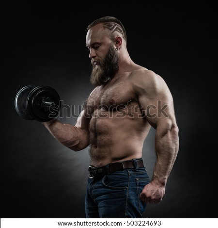 Strong bodybuilder with six pack, perfect abs, shoulders, biceps, triceps and chest. Power athletic bearded man in training pumping up muscles with dumbbell.