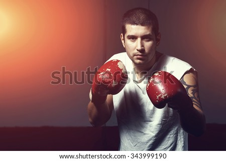 Strong boxer on wall background boxing hall. Hispanic latino man. Brawny man in boxing gloves. Male aggressive look with in hand boxing gloves. Male sportsman. toned image - stock photo