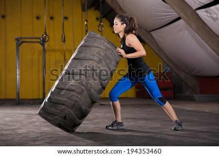 Strong brunette making almost no effort in flipping a big tire in a cross-training gym - stock photo