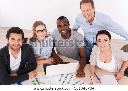 Strong business team. Top view of group of business people in casual wear sitting together at the table and smiling at camera - stock photo