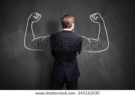 strong businessman standing in front of a chalkboard - stock photo