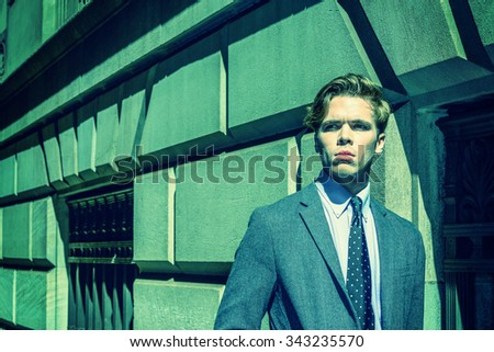 Strong color filtered look with cyan tint and harsh sunshine to represent young man attitude - confident, determination, success. American College Student traveling, studying in New York. City Boy.  - stock photo