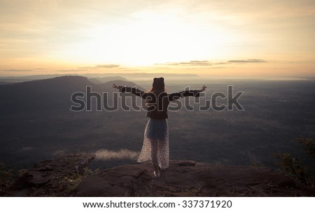 strong confidence woman open arms under the sunrise at mountain - stock photo