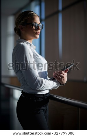 Strong, confident, business woman standing in an office building, holding tablet computer - stock photo