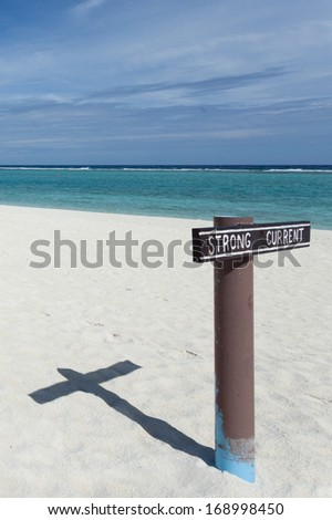 Strong current alert sign in white sand and blue sea of Maldive Islands - stock photo