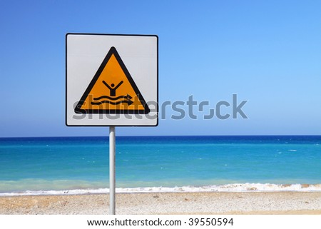 Strong current sign on beach with blue sea in the background - stock photo