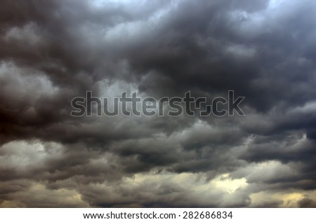 Strong dark gray dramatic sky with large clouds - stock photo