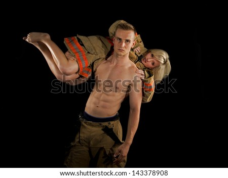 Strong fireman with a beautiful blonde victim over his shoulders as they look into the camera. - stock photo